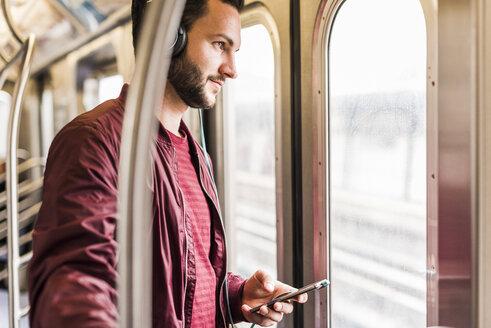 Young man in subway wearing headphones - UUF09159