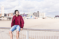 USA, New York City, man sitting on railing on Coney Island wearing headphones - UUF09162