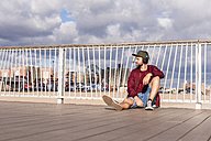 USA, New York City, man sitting on bridge on Coney Island wearing headphones - UUF09165