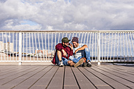 USA, New York City, two friends sitting on bridge on Coney Island sharing headphones - UUF09168