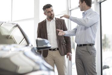 Car dealer talking to client in showroom - ZEF11528