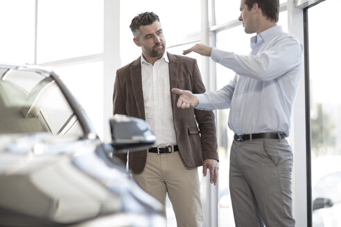 Car dealer talking to client in showroom - ZEF11528