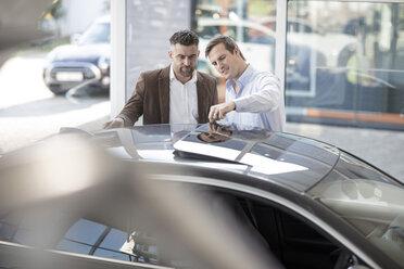 Car dealer talking to client at car dealership - ZEF11531