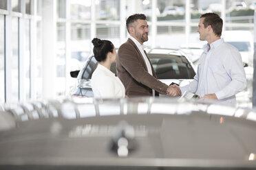 Car dealer shaking hands with man in car dealership - ZEF11537