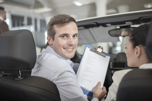 Smiling car dealer with clipboard and woman in car - ZEF11543