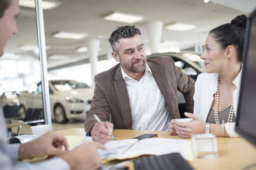 Car dealer and couple sitting at desk with agreement forms in showroom - ZEF11552