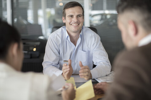 Smiling car dealer and couple sitting at desk at car dealership - ZEF11555