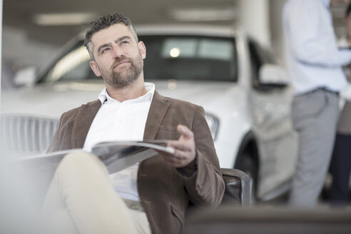 Man sitting with magazine at car dealership - ZEF11558