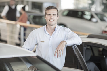 Portrait of confident car dealer in showroom - ZEF11564