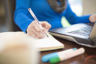 Woman at desk with laptop writing in notebook - ZEF11576