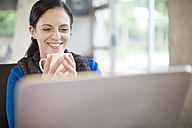 Smiling woman at desk with coffee cup and laptop - ZEF11579