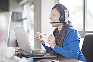 Smiling woman at desk with laptop and headset - ZEF11582