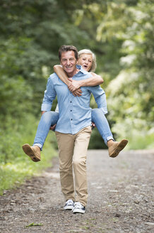 Smiling senior man giving his wife a piggyback ride on forest track - HAPF01076