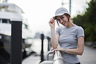 Portrait of smiling woman wearing basecap - GIOF01601