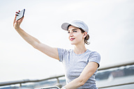 Woman with basecap taking selfie with cell phone - GIOF01607