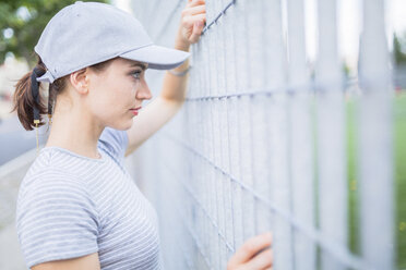 Woman wearing basecap looking through fence - GIOF01616