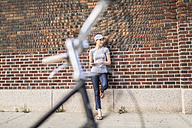 Woman with smartphone leaning against brick wall - GIOF01619