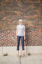 Smiling woman jumping in the air in front of brick wall - GIOF01622