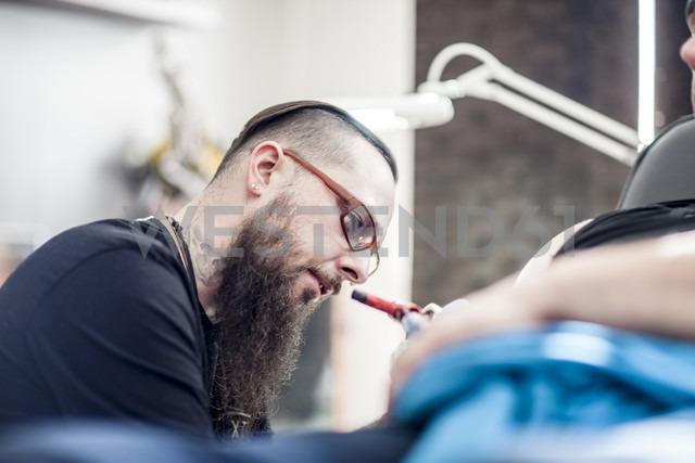 Tattoo artist in studio at work - ZEF11589