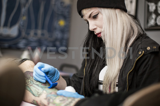 Female tattoo artist shaving leg before tattooing - ZEF11592