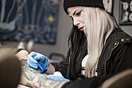 Female tattoo artist shaving leg before tattooing - ZEF11592