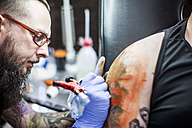 Tattoo artist tattooing an arm - ZEF11598