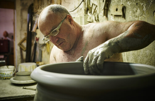 Potter in workshop working on large terracotta vase - DIKF00233