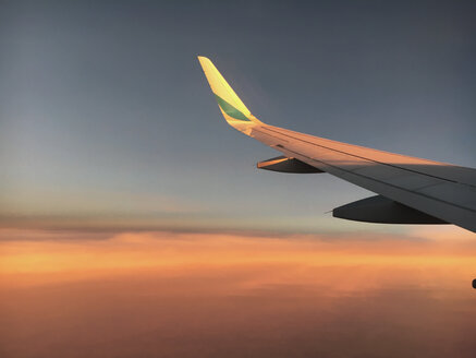 Airplane wing over clods at sunset - BMAF00299