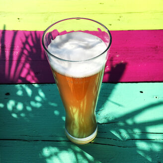 Glass of wheat beer on multicolored background - BMAF00302