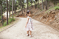 Little girl standing on forest track - VABF00817