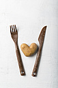 Potato in heart shape between fork and knife on white background - MYF01836