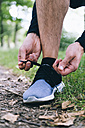 Jogger tying his shoes - BOYF00634