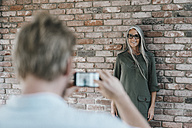 Man taking picture of smiling woman with long grey hair at brick wall - KNSF00436
