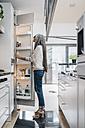 Woman in kitchen looking in fridge - KNSF00442