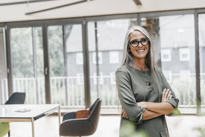 Portrait of smiling woman with long grey hair in office - KNSF00448