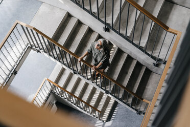 Woman with long grey hair in staircase - KNSF00454