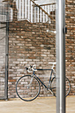 Bicycle at brick wall in office - KNSF00457