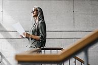 Woman with long grey hair holding document - KNSF00460