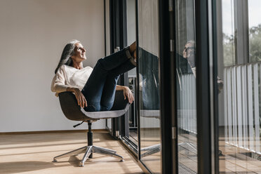 Woman with long grey hair sitting on chair at the window - KNSF00472
