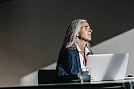Businesswoman at desk enjoying sunlight - KNSF00487