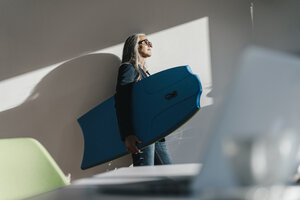 Businesswoman in office holding surboard enjoying sunlight - KNSF00490
