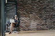 Smiling woman with long grey hair using laptop - KNSF00496