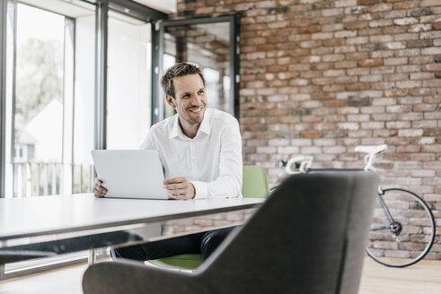Smiling businessman using laptop in office - KNSF00508