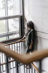 Woman with long grey hair looking out of window in staircase - KNSF00526