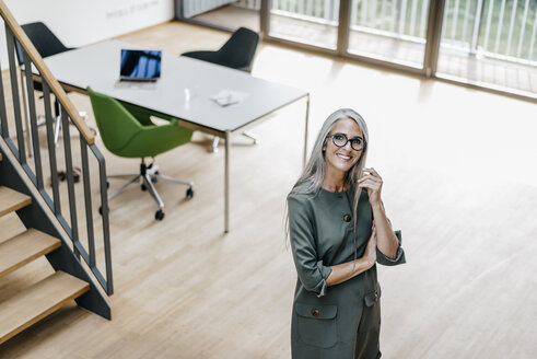 Portrait of smiling woman with long grey hair in office - KNSF00541