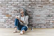 Woman with long grey hair sitting on the floor at brick wall - KNSF00550