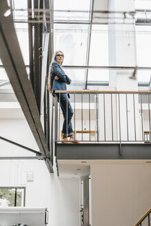 Confident businesswoman with long grey hair in a loft - KNSF00559
