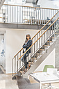 Smiling businesswoman with long grey hair standing on stairs - KNSF00562