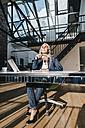 Businesswoman at desk enjoying sunlight - KNSF00574