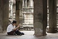 Cambodia, Siem Reap, Angkor Wat, tourist taking pictures of temple with smartphone - MADF01214